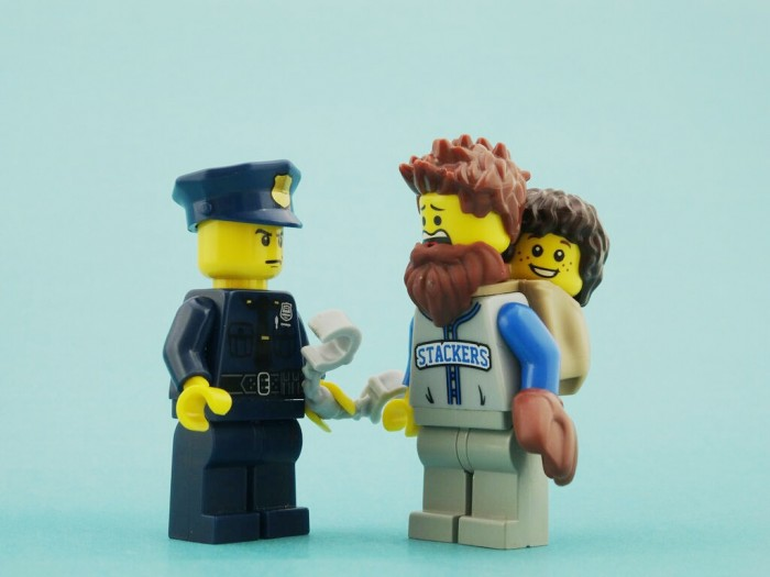 A father was mistakenly arrested when a neighbour didn't recognise him in a beard and called police to report the father carrying his son in a grocery bag.